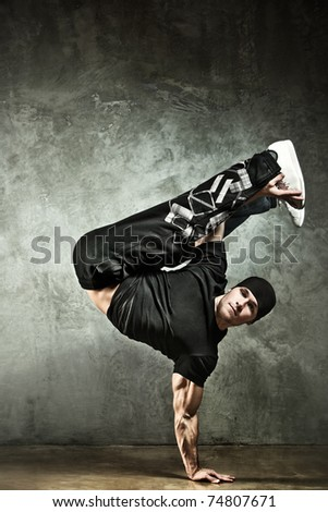 Young strong man break dance. On wall background.