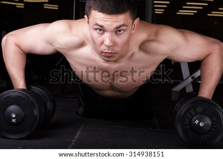Young strong man pushed, having rested on the dumbbell. The muscles on his arm stretched and embossed. Young muscular athlete trains in the gym. - stock photo