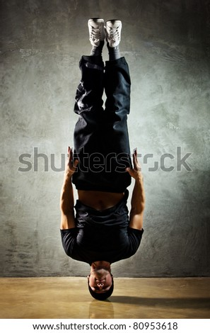 Young strong man standing on head. - stock photo
