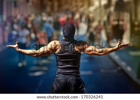 Young strong man standing on street against people. - stock photo
