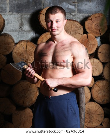 Young strong man with hatchet and a lot of woods - stock photo
