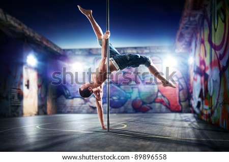Young strong pole dance man on urban background. - stock photo