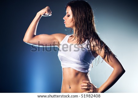 Young strong sexy woman showing her muscles. - stock photo
