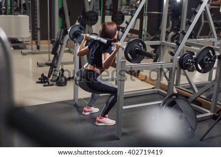 Young strong woman doing squats at the gym in front of a mirror with a barbell on her back - stock photo