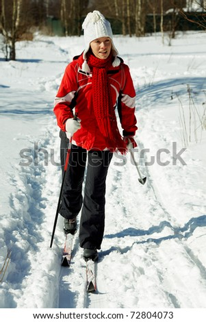 young strong woman is skiing in the forest - stock photo