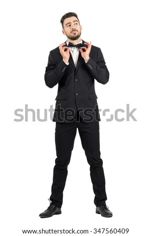 Young stubble groom adjusting bow tie looking up. Full body length portrait isolated over white studio background.  - stock photo