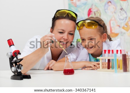 Young student and teacher in elementary science class doing a chemical experiment - stock photo