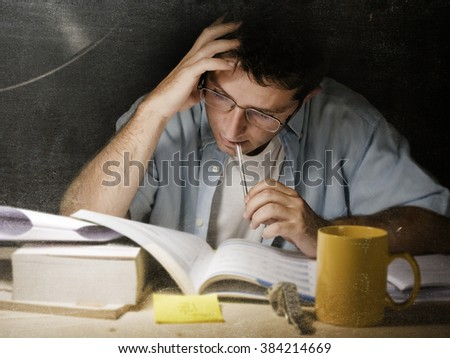 Young student at home desk reading biting pen studying at night with pile of books and coffee cup preparing exam in university education concept in edgy  light set  - stock photo