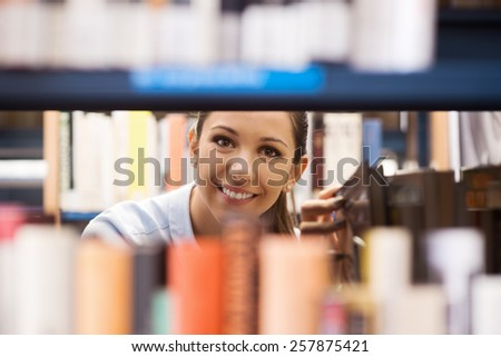 Young student at the library searching for books and peeking through bookshelves - stock photo