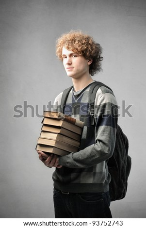 Young student carrying a stack of books - stock photo