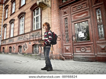 Young student carrying some books out of a school - stock photo
