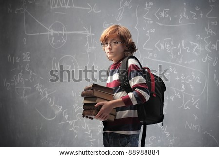 Young student carrying some books with blackboard in the background - stock photo