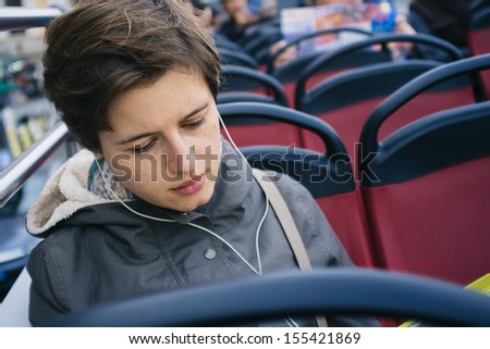 young student commuter listening to the music on the bus - stock photo