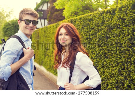 Young student couple  smiling and looking to camera  in a city while taking a walk.Young students outdoors  walking on a city street in a sunny day.Weekend,City,Life style - stock photo