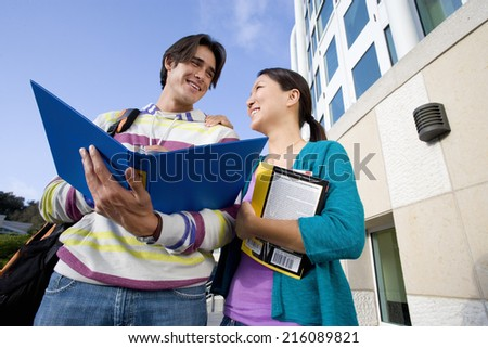 Young student couple smiling at each other, man with open folder, low angle view - stock photo