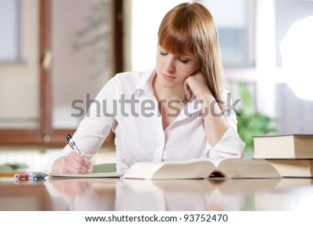 Young student doing her homework at a table