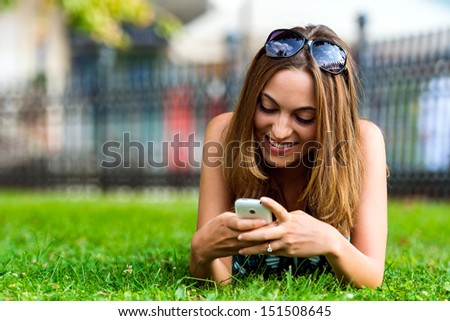 Young Student Girl (21) Browsing The Internet With Her Cell Phone in City Park - stock photo