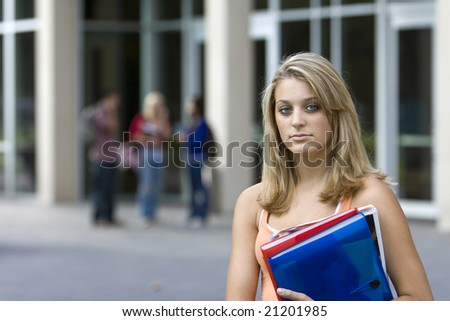 Young student girl holding her books outside of school. Horizontally framed photo. - stock photo