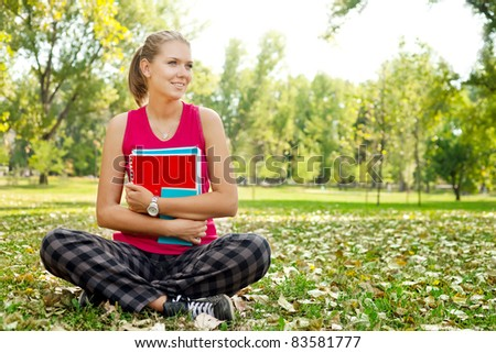 young student girl in park hugging books