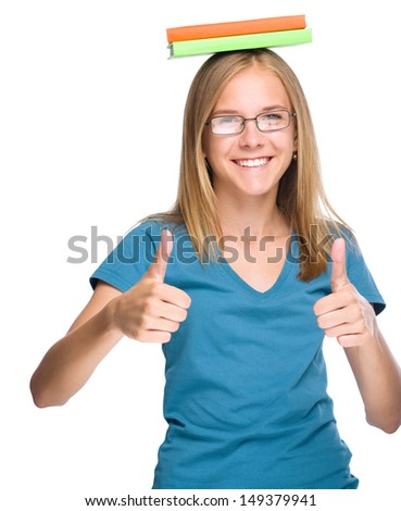 Young student girl is holding exercise books on her head while showing thumb up gesture using both hands, isolated over white - stock photo