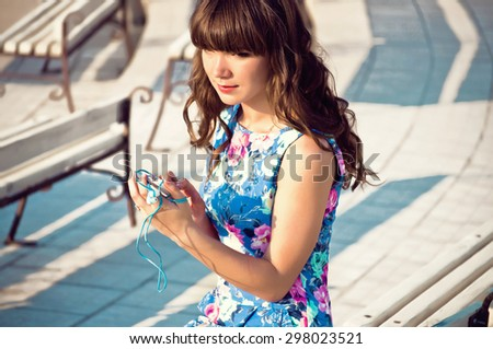 young student girl listening to music in the park - stock photo