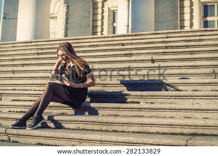 Young student girl sitting outdoor near the college with tablet in hands - stock photo