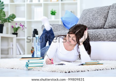 Young student girl with books on floor studying - stock photo