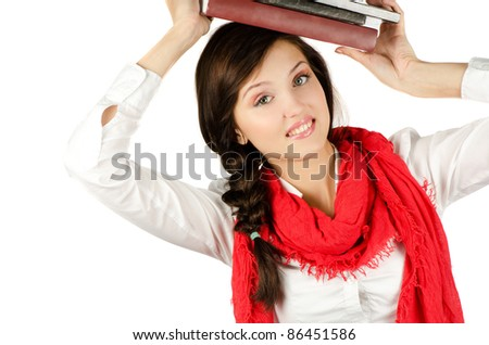 Young student girl with her books in hand at head, smiling and looking at the camera - stock photo