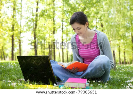 young student girl with laptop learning in park