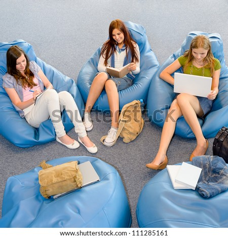 Young student girls resting on blue beanbags at library - stock photo