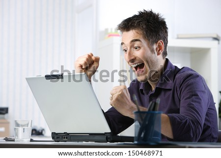 Young student happy after she saw the good news in front at laptop - stock photo