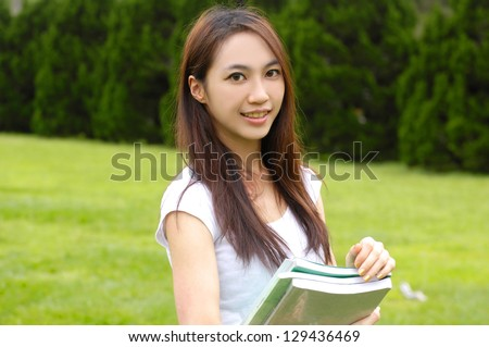 young student holding book at campus