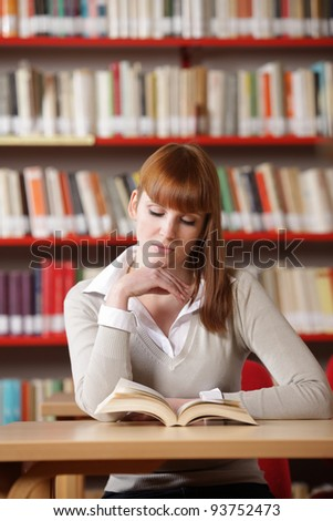 Young student in a library with book - stock photo