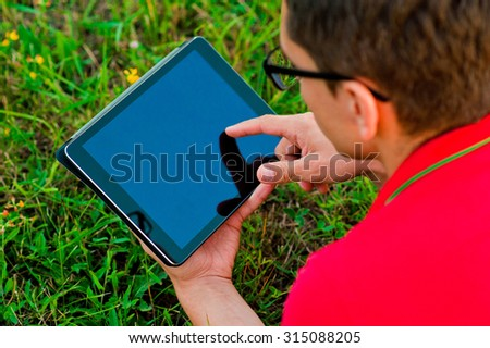 young student in a park holding a touch screen device - stock photo