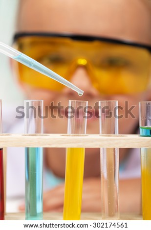 Young student in chemistry class - closeup on test tubes with colorful chemical solutions - stock photo