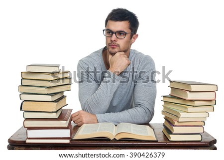 Young student in glasses sitting at a table, reading a lot of books, isolated on white