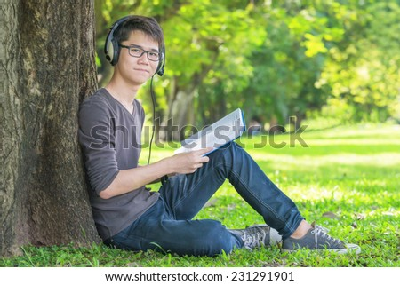 Young student in park listening to music on headphones - stock photo