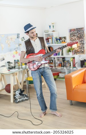 young student is playing guitar in his apartment