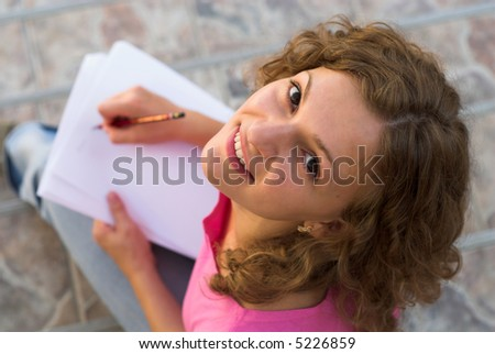 Young student is preparing to the lesson outdoors - stock photo