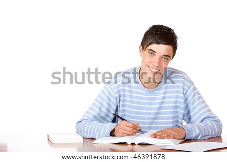 Young student is sitting on desk with open book and learns for his exams. He looks smiling into camera. Isolated on white.