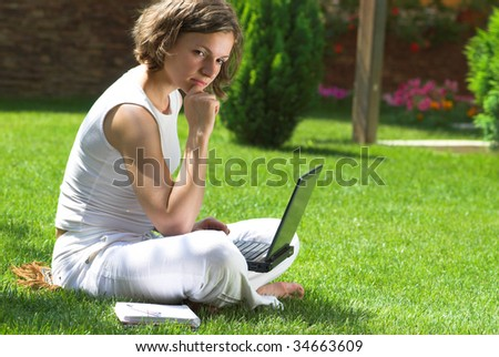 Young student is thinking on homework on campus grass