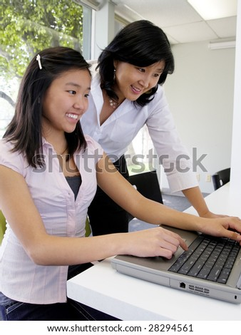 Young student learning computer skills with the help of her teacher - stock photo