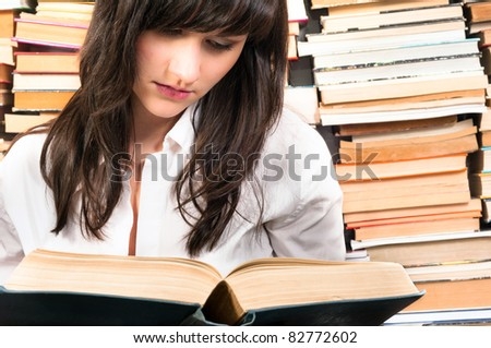 Young student learning from a book - stock photo