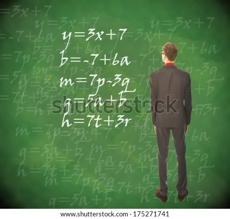 Young student looking at chalkboard with mathematics - stock photo