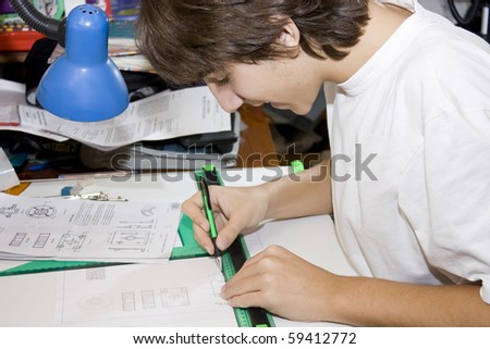 Young student makes technical drawing on a board with their tools - stock photo