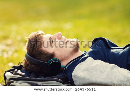 Young student, man relaxing smiling while lying on grass and listening to music.Player.Music,Relax - stock photo