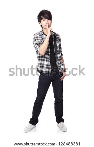 young student man with his finger on his lips asking quiet in full length isolated on white background, asian model - stock photo