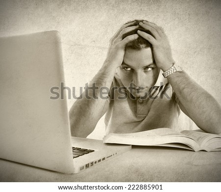young student man worried frustrated and overwhelmed studying exam with book and computer laptop with hands on head in college education stress on grunge black and white - stock photo