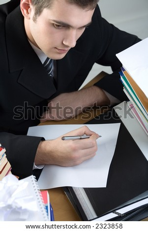 Young student or businessman writing something on blank paper sheet, puzzled
