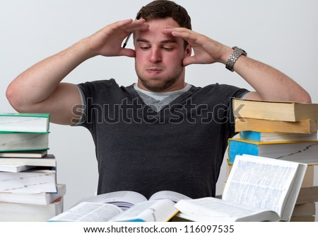 Young Student overwhelmed with studying with piles of books in front of him